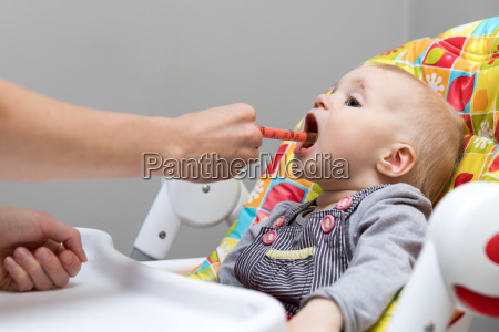 mother giving cough syrup with syringe
