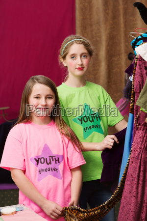 girls standing near costumes in youth