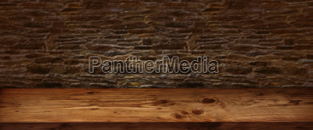 rustic wooden table with stone wall