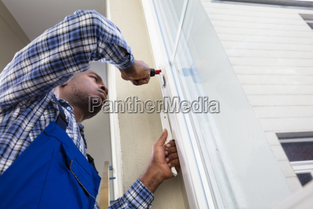 handyman in uniform fixing glass window