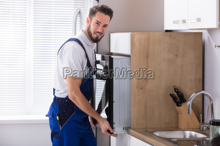 male electrician fixing oven