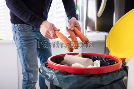 person throwing carrot in dustbin