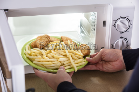 person putting fried food inside microwave