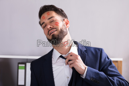businessman with lipstick kiss marks on