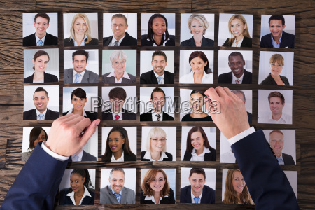 businesspersons hand choosing photograph of candidate