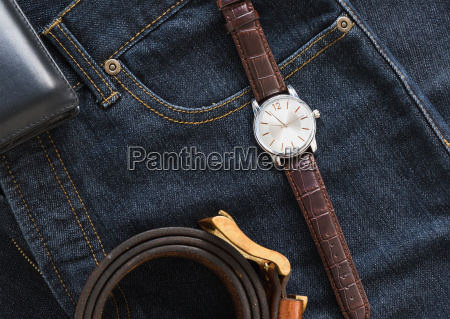 wristwatch and wallet on denim jeans