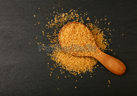 wooden spoon of brown cane sugar