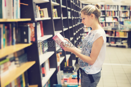 young woman choosing a book to