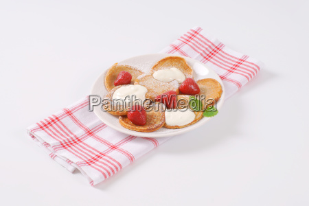 small pancakes with cream and strawberries