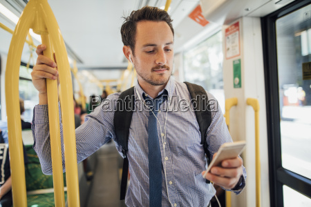 businessman, commuting, by, tram, in, melbourne - 23509012
