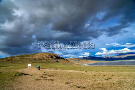 solo female cyclist and tibetan lake