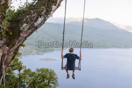 man sitting on swing against lake