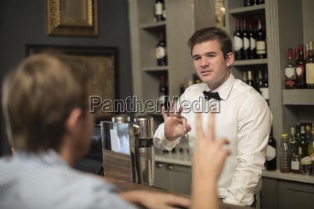barkeeper behind bar taking an order