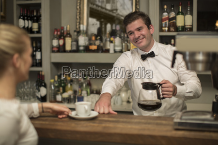 smiling barkeeper preparing cup of coffee