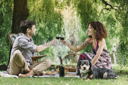 couple with dog having a picnic
