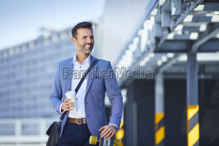 portrait of businessman with longboard and