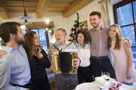 senior man playing accordion for happy