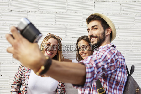 three friends taking photos at white