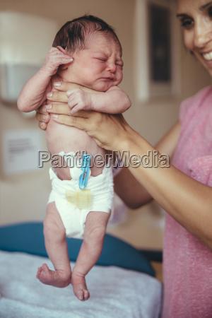 newborn baby girl in hospital holding