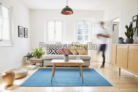 man walking in bright modern living