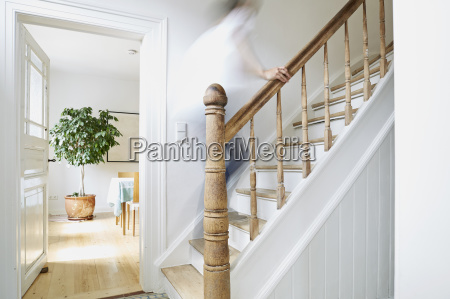 man going upstairs on wooden stairs