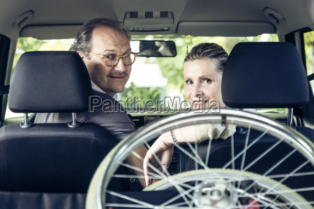 smiling couple in car with wheelchair