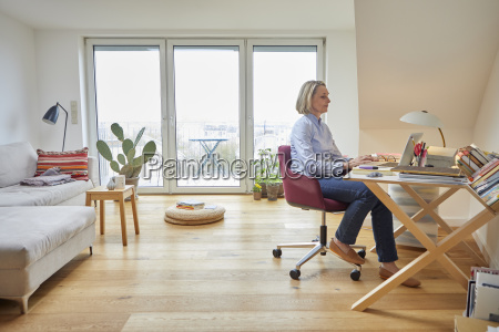 mature woman at home using laptop