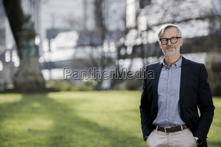 grey haired businessman in city park