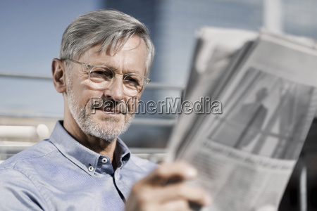grey haired man reading newspaper