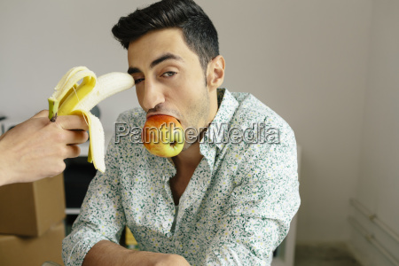 portrait of casual businessman with banana