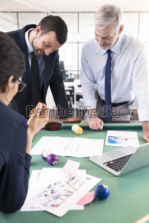 business people standing at pool table