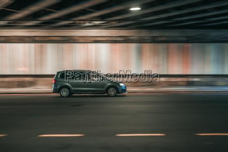 car driving under a bridge in