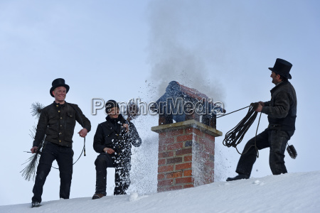 three chimney sweeps working on roof