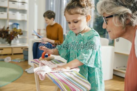 teacher watching girl ironing in kindergarten