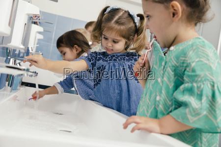 children brushing their teeth in bathroom