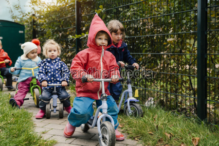 children using scooters in garden of
