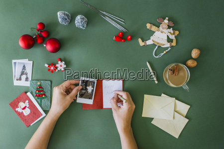 womans hands writing christmas card