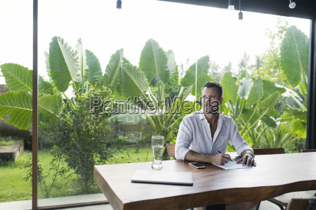 mature man sitting at table in