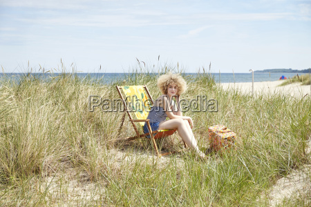 young woman sitting on beach chair