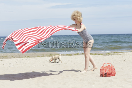 young woman with blowing beach towel