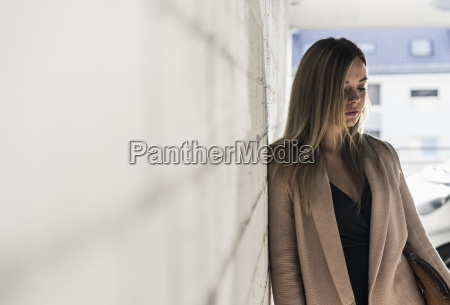 thoughtful young woman leaning against a