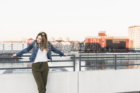 young woman leaning against railing in