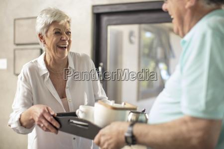 happy senior woman serving coffee on