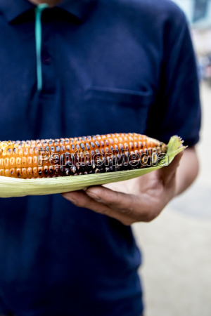 nepali man holding roasted corn at