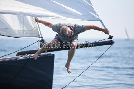 man at bow of sailboat trying