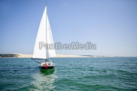 sailboat sailing with dune of pilat