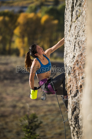 female climber reaching into chalk bag