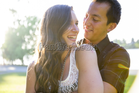 young couple smiling while embracing green