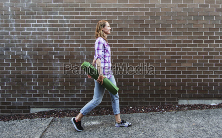 young woman walking down sidewalk carrying