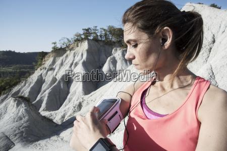 woman wearing sportswear using smartphone in